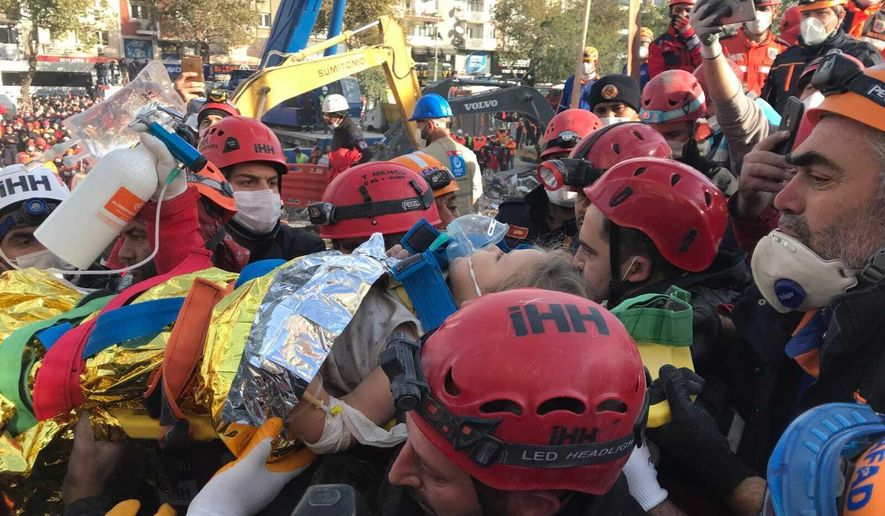 In this photo provided by Turkey's IHH humanitarian aid group, Ayda Gezgin is carried by members of rescue services and medics after she was taken out of the rubble of her collapsed building, in Izmir, Turkey, Tuesday, Nov. 3, 2020. Rescuers in the Turkish coastal city pulled Gezgin out alive from the rubble, some four days (91 hours) after a strong earthquake hit Turkey and Greece. The girl was taken into an ambulance, wrapped in a thermal blanket, amid the sounds of cheers and applause from rescue workers. (IHH via AP)