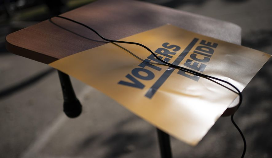 """A sign that reads """"Voters Decide"""" is placed next to a hanging microphone as people gather at the Civic Center Park while waiting for the results of election, Wednesday, Nov. 4, 2020, in Kenosha, Wis. (AP Photo/Wong Maye-E)"""