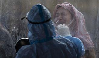 A woman reacts as a Kashmiri health worker takes a nasal swab sample to test for COVID-19 in Srinagar, Indian controlled Kashmir, Wednesday, Nov. 4, 2020. (AP Photo/Mukhtar Khan)