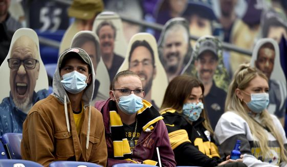 In this Nov. 1, 2020, file photo, specators wear a face masks to protect against COVID-19 during the first half of an NFL football game between the Baltimore Ravens and the Pittsburgh Steelers, in Baltimore. A new set of rules are coming in just about every sport, almost all with enhanced health and safety in mind. If they work, games could get out of bubbles and return to arenas and stadiums with some fans in attendance sometime soon. Perhaps more importantly, they could also provide some common-sense solutions to virus issues in the real world.(AP Photo/Gail Burton, File)  **FILE**