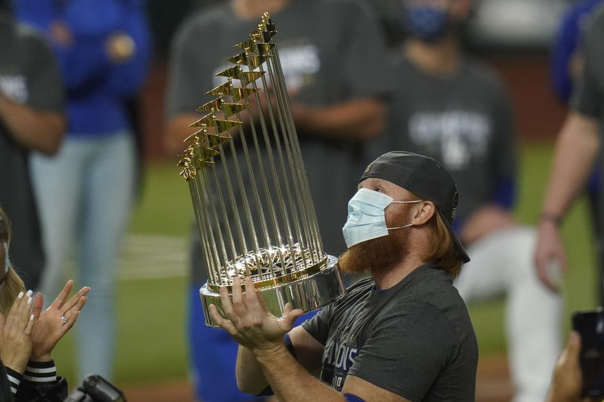 In this Tuesday, Oct. 27, 2020, file photo, Los Angeles Dodgers third baseman Justin Turner celebrates with the trophy after defeating the Tampa Bay Rays 3-1 to win the baseball World Series in Game 6 in Arlington, Texas. Baseball nearly made it through its version of playoff bubbles unscathed; two innings before the World Series ended, Justin Turner of the now-champion Los Angeles Dodgers Turner was pulled from the game after MLB was notified that he had tested positive for COVID-19. (AP Photo/Eric Gay, File)  **FILE**