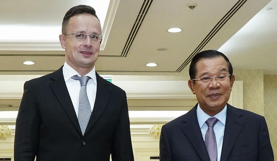 Hungarian Foreign Minister Peter Szijjarto, left, poses with Cambodian Prime Minister Hun Sen for a photo prior to a meeting at Peace Palace in Phnom Penh, Cambodia, Tuesday, Nov. 3, 2020. Szijjarto tested positive for the coronavirus after arriving in Thailand for an official visit, Thai and Hungarian officials said Wednesday, Nov. 4, 2020. (Pool Photo via AP)