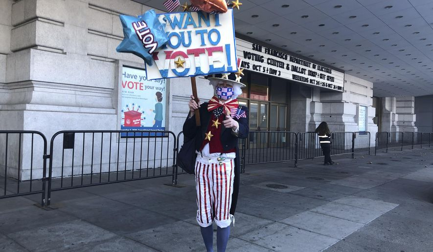 Daniel Johnson decided to spend part of his afternoon walking around San Francisco's voting center near City Hall dressed in an Uncle Sam costume and holding a sparkly sign urging people to vote.Tuesday, Nov. 3, 2020 in San Francisco, Cal. Johnson, an archivist from San Francisco, dropped off his ballot at the center on Friday but after he was unable to do phone banking or join postcard writing campaigns before the election, he decided he would try to encourage people to vote. (AP Photo/Olga R. Rodriguez)