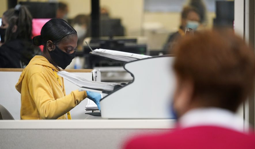 A county election worker scans mail-in ballots at a tabulating area as an observer watches at the Clark County Election Department, Thursday, Nov. 5, 2020, in Las Vegas. (AP Photo/John Locher)
