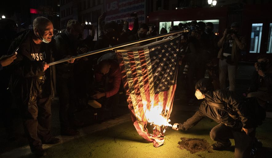 Protesters burn a national flag during a march following the presidential election Wednesday, Nov. 4, 2020, in Portland, Ore. (AP Photo/Paula Bronstein)