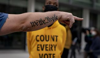 "The tattoo ""We The People,"" a phrase from the United States Constitution, decorates the arm of Trump supporter Bob Lewis, left, as he argues with counter protestor Ralph Gaines while Trump supporters demonstrate against the election results outside the central counting board at the tcf Center in Detroit, Thursday, Nov. 5, 2020. (AP Photo/David Goldman)"