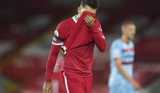 Liverpool's Roberto Firmino wipes his face during the English Premier League soccer match between Liverpool and West Ham United at Anfield stadium in Liverpool, England, Saturday, Oct. 31, 2020. (AP Photo/Jon Super, Pool)