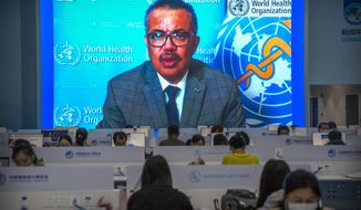 Journalists wearing face masks to protect against the coronavirus work as video screens show World Health Organization chief Tedros Adhanom Ghebreyesus delivering a prerecorded address to the opening ceremony of the China International Import Expo in Shanghai, Wednesday, Nov. 4, 2020. The expo, one of China's largest annual trade fairs, kicks off on Thursday as the ongoing COVID-19 pandemic has largely been controlled within China. Ghebreyesus announced this week that he would self-quarantine after being identified as a contact of a person who tested positive for COVID-19. (AP Photo/Mark Schiefelbein)