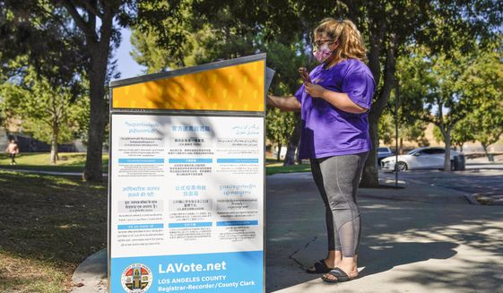 In this Oct. 14, 2020, file photo, a citizen drops her ballot at an official ballot drop box in Santa Clarita, Calif. California's leaders are considering making voting by mail a permanent option for all of its registered voters. This year, the state required county elections officials to mail a ballot to all registered voters ahead of the election. (AP Photo/Marcio Jose Sanchez, File)