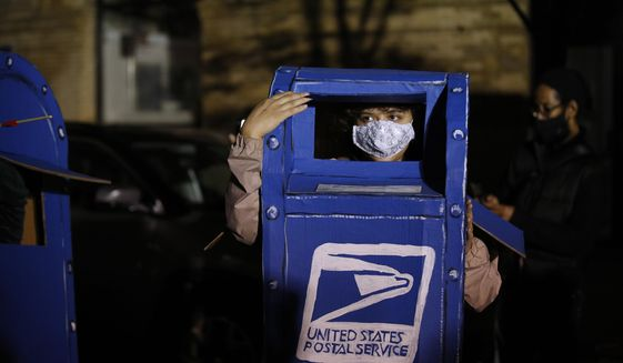 A person wears a costume of a U.S. Postal Service mailbox while demonstrating outside the Pennsylvania Convention Center where votes are being counted, Thursday, Nov. 5, 2020, in Philadelphia, following Tuesday's election. (AP Photo/Rebecca Blackwell)  **FILE**