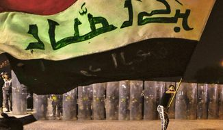 A protester waves an Iraqi flag while Security forces surround the protest site during ongoing anti-government protests in Basra, Iraq, Wednesday, Nov. 4, 2020. (AP Photo/Nabil al-Jurani)