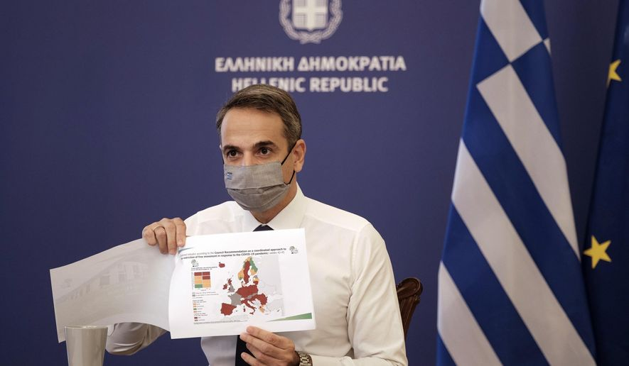 """In this photo provided by the Greek Prime Minister's Office, Greece's Prime Minister Kyriakos Mitsotakis shows a map of Europe during his announcement on the country's new lockdown in Athens, Thursday, Nov. 5, 2020. Mitsotakis has announced a nationwide three-week lockdown starting Saturday morning, saying that the increase in the coronavirus infections must be stopped before Greece's health care system comes under """"unbearable"""" pressure. (Dimitris Papamitsos/Greek Prime Minister's Office via AP)"""