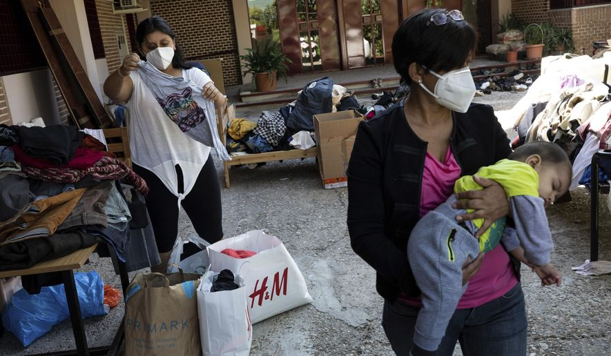 Residents of the southern neighbourhood of Vallecas pick clothes from a donation program at a Catholic parish in Madrid, Spain, Thursday, Oct. 1, 2020. Spain's government expects the economy to contract 11.2% this year, while the International Monetary Fund puts the drop at 12.8%, the highest rate among developed economies. (AP Photo/Bernat Armangue)
