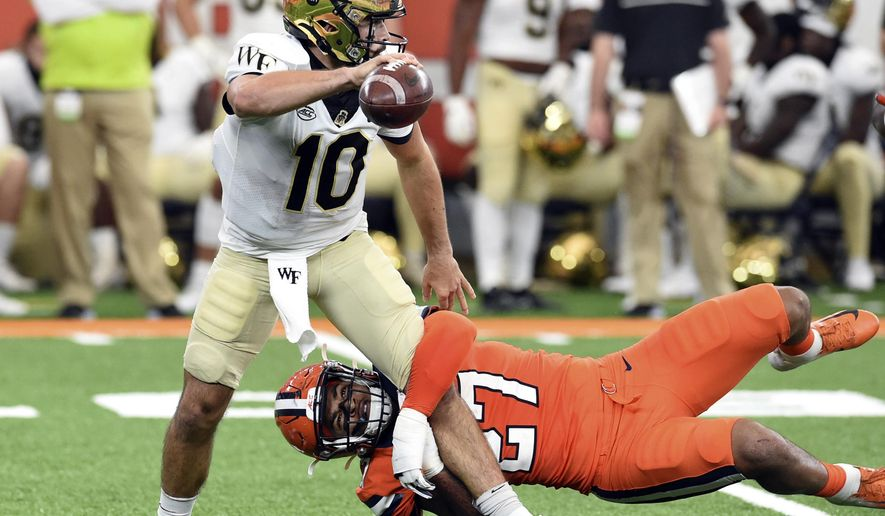 Syracuse linebacker Stefon Thompson (27) puts pressure on Wake Forest quarterback Sam Hartman (10) during an NCAA college football game Saturday, Oct. 31, 2020, in Syracuse, N.Y. (Dennis Nett/The Post-Standard via AP)