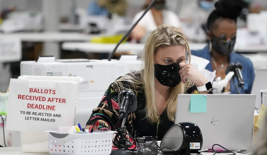 Workers at the Gwinnett County Voter Registration and Elections Headquarters, Friday, Nov. 6, 2020, in Lawrenceville, near Atlanta. (AP Photo/John Bazemore)  **FILE**