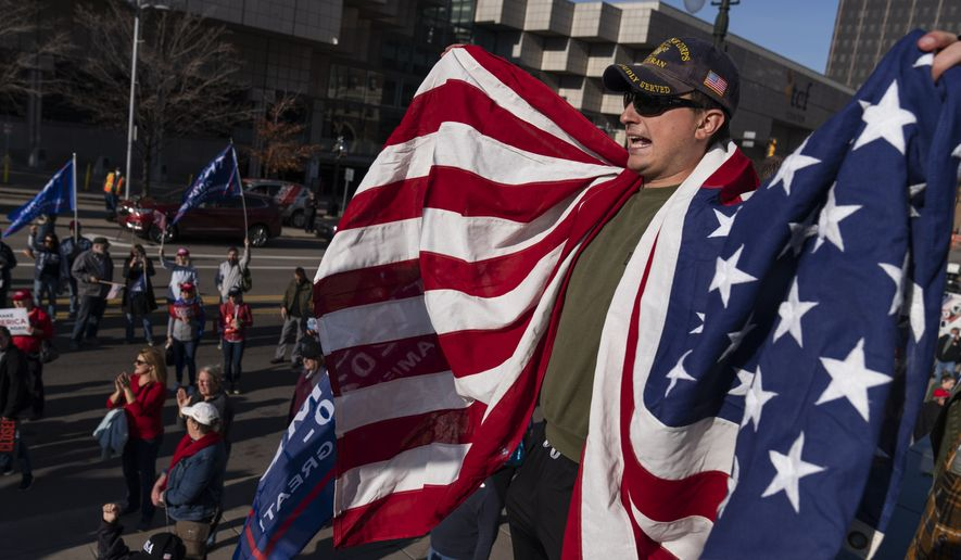 Trump supporter Michael Foy is draped in an American flag during a protest against the election results outside the central counting board at the TCF Center in Detroit, Friday, Nov. 6, 2020. (AP Photo/David Goldman)