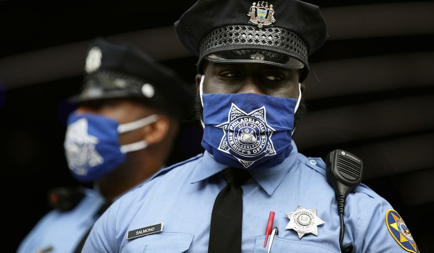 Police officers stand outside the Pennsylvania Convention Center where votes are being counted, Friday, Nov. 6, 2020, in Philadelphia. (AP Photo/Rebecca Blackwell)