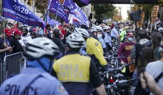 Police separate President Donald Trump supporters and pro-vote counting demonstrators outside the Philadelphia Convention Center three days after the presidential election polls closed as they await tabulation results, Friday, Nov. 6, 2020, in Philadelphia. (AP Photo/John Minchillo)