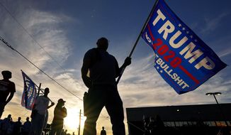 EDS NOTE: OBSCENITY - A Trump supporter stands outside the Maricopa County Recorder's Office, where votes in the general election are being counted, Thursday, Nov. 5, 2020, in Phoenix. (AP Photo/Matt York)
