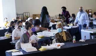An election worker handles ballots as vote counting in the general election continues at State Farm Arena on Thursday, Nov. 5, 2020, in Atlanta. (AP Photo/Brynn Anderson)