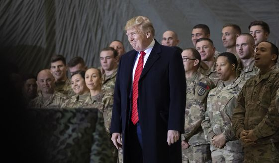 In this Nov. 28, 2019, photo, President Donald Trump smiles before addressing members of the military during a surprise Thanksgiving Day visit at Bagram Air Field, Afghanistan. (AP Photo/Alex Brandon) **FILE**