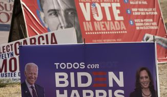 A campaign sign supporting Democratic presidential candidate former Vice President Joe Biden and running mate Kamala Harris stands in front of a vote sign showing former President Barack Obama near the Clark County Election Department in North Las Vegas, Nev., Friday, Nov. 6, 2020. (AP Photo/Jae C. Hong)