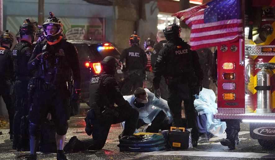 Emergency crews attend an injured man detained by police during a protest after the Nov. 3 elections in front of the east precinct station, Wednesday, Nov. 4, 2020, in Seattle. (AP Photo/Ted S. Warren)