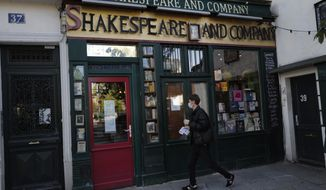 """A man walks by the closed English and American literature Shakespeare and Co. bookstore in Paris, France, Thursday, Nov. 05, 2020. Iconic Parisian bookshop Shakespeare and Co. has launched a support appeal to its readers after its owners say that coronavirus-linked losses, and a crippling months-long lockdown, have left the future of the veritable institution in doubt. """"We've been minus 80 percent since the first confinement in March, so at this point we've used all our savings,"""" Sylvia Whitman, daughter of the shop's co-founder George Whitman, told the Associated Press. (AP Photo/Francois Mori)"""