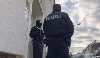 Police officers are standing outside an apartment building during a search in Osnabrueck, Germany, Friday, Nov. 6, 2020. German police have raided the homes and businesses of four men linked to the Islamic State sympathizer who carried out a deadly attack in Vienna this week. Federal police said Friday that officers, including members of the anti-terrorism unit GSG9, searched premises in Osnabrueck, Kassel and Pinneberg county. (Festim Beqiri/TV7News/dpa via AP)