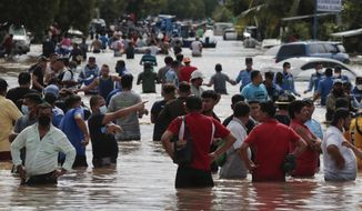 Residents wade through a flooded road in the aftermath of Hurricane Eta in Planeta, Honduras, Thursday, Nov. 5, 2020. The storm that hit Nicaragua as a Category 4 hurricane on Tuesday had become more of a vast tropical rainstorm, but it was advancing so slowly and dumping so much rain that much of Central America remained on high alert. (AP Photo/Delmer Martinez)