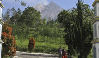 FILE - In this May 11, 2018, file photo, villagers walk along a road Mount Merapi is seen in the background in Pemalang, Central Java, Indonesia. Indonesian authorities are raising the danger level for the volatile Mount Merapi volcano on densely populated Java island and ordering a halt to tourism and mining activities. (AP Photo/Agung Nugroho, File)