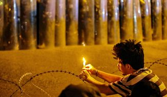 An anti-government protester lighting a candle while Security forces surround the protest site during ongoing protests in Basra, Iraq, Wednesday, Nov. 4, 2020. (AP Photo/Nabil al-Jurani)