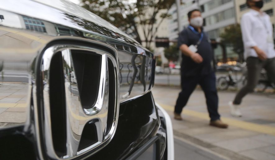 People walk by a Honda car displayed in front of a Honda Motor Co. showroom in Tokyo, Monday, Nov. 2, 2020. Japanese automaker Honda reported Friday, Nov. 6, 2020 that its profit rose 23% from a year earlier in the last quarter, despite a pandemic that has slammed businesses around the world. (AP Photo/Koji Sasahara)