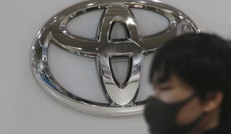 A visitor wearing a face mask to help curb the spread of the coronavirus walks by the logo of Toyota Motor Corp. at its showroom in Tokyo, Monday, Nov. 2, 2020. Toyota's July-September profit fell 11% as the coronavirus pandemic slammed global demand, but Japan's top automaker appeared to be holding up well, compared to weaker rivals that have sunk into the red. (AP Photo/Koji Sasahara)