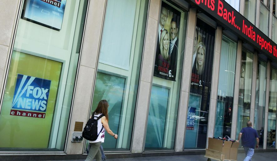 In this file photo, people pass the News Corporation headquarters building and Fox News studios in New York on Aug. 1, 2017.  (AP Photo/Richard Drew, File)  **FILE**
