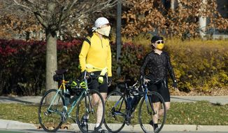 People walk their bicycles while crossing the street in Evanston, Ill., Friday, Nov. 6, 2020. Illinois Gov. J.B. Pritzker said he would again impose tougher statewide restrictions if the latest resurgence of coronavirus cases continues to escalate. (AP Photo/Nam Y. Huh)