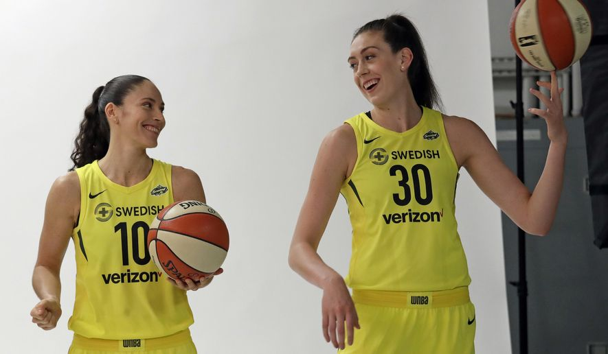 FILE - In this May 9, 2018, file photo, Seattle Storms players Sue Bird, left, and Breanna Stewart smile as pose a photo session during the WNBA basketball team's media day in Seattle. The Storm teammates are among a half-dozen WNBA players who have frozen their eggs according to the players union. (AP Photo/Elaine Thompson, File)
