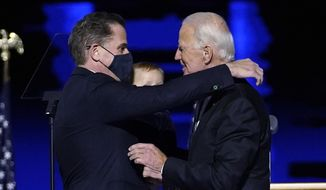 President-elect Joe Biden, right, embraces his son Hunter Biden, left, Saturday, Nov. 7, 2020, in Wilmington, Del. (AP Photo/Andrew Harnik, Pool)