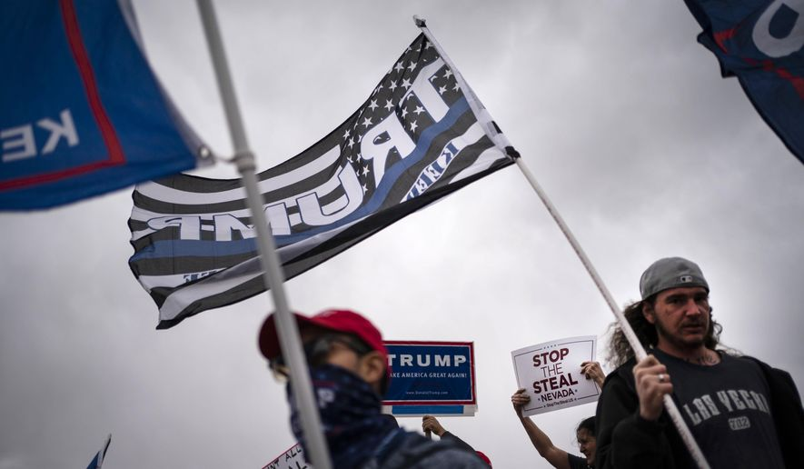 Supporters of President Donald Trump stand outside of the Clark County Elections Department in North Las Vegas, Saturday, Nov. 7, 2020. (AP Photo/Wong Maye-E)