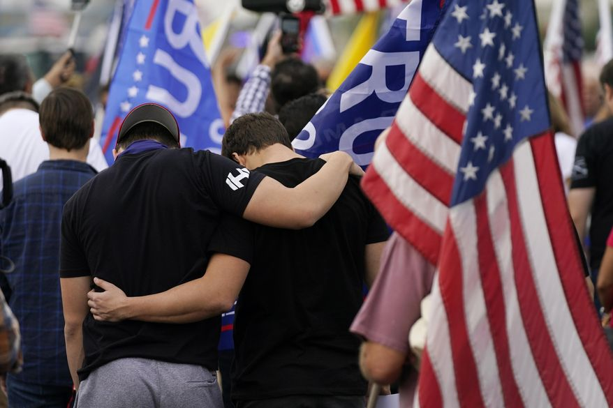 Supporters of President Donald Trump pause in prayer at a rally outside the Maricopa County Recorder's Office, Friday, Nov. 6, 2020, in Phoenix. (AP Photo/Ross D. Franklin)