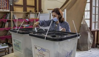 A woman casts her vote on the first day in the second and final stage of the country's parliamentary elections in Cairo, Egypt, Saturday, Nov. 7, 2020. Egyptians began voting on Saturday after a relatively low turnout in the first stage that embarrassed the government of President Abdel-Fattah el-Sissi. (AP Photo/Nariman El-Mofty)