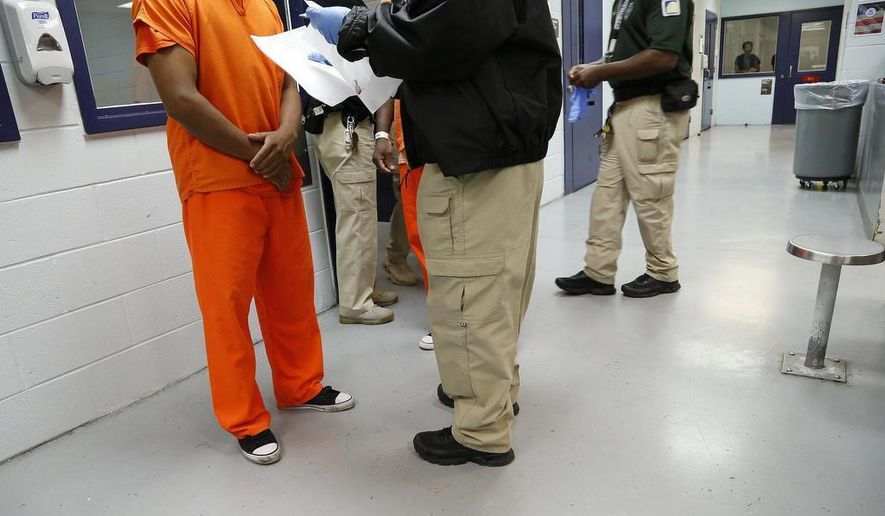 """This Sept. 24, 2015 photo shows a detainee is processed by a guard inside the Krome Detention Center in Miami. Under the Trump administration, the country has become increasingly inhospitable for undocumented immigrants and those seeking asylum. But it has also recalibrated the treatment of legal permanent residents — referred to as """"green card"""" holders — and naturalized citizens, affording zero tolerance for transgressions that would have been of little interest under previous administrations.  (José A. Iglesias/Miami Herald via AP)"""