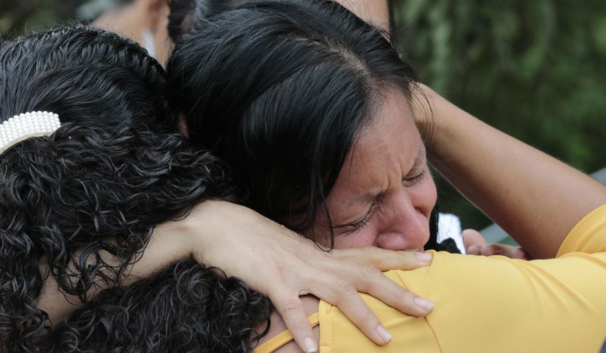 Mirian Najera is comforted upon learning about the death of her mother Maria Mejia, in Planeta, Honduras, Friday, Nov. 6, 2020. When the brown waters of the Chamelecon river poured into San Pedro Sula's Planeta neighborhood before dawn Thursday, Najera fled her home in the dark with her two children and her mother. But while she held tight to her children, the current swept away her mother. (AP Photo/Delmer Martinez)