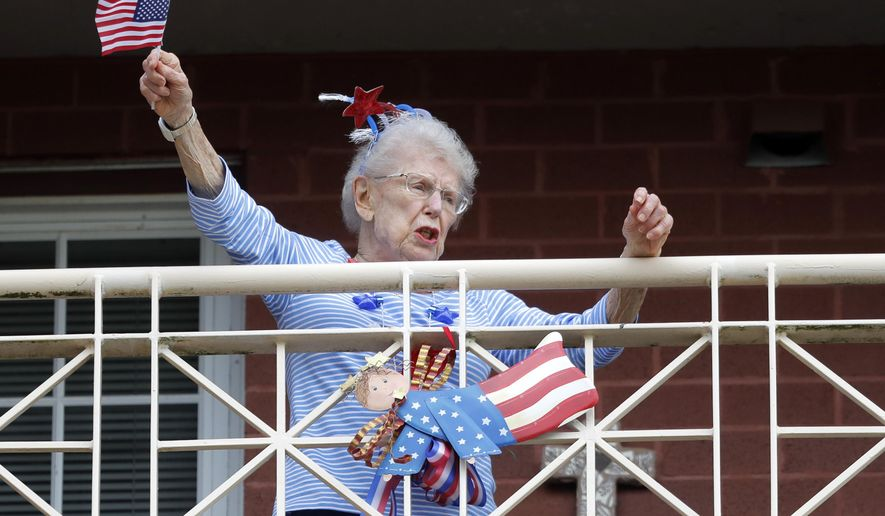 A resident of the Lambeth House, where a cluster of the coronavirus has formed, reacts from her balcony as opera singers Irini Hymel and Bryan Hymel sing to the quarantined residents in New Orleans, Friday, March 20, 2020.  (AP Photo/Gerald Herbert)
