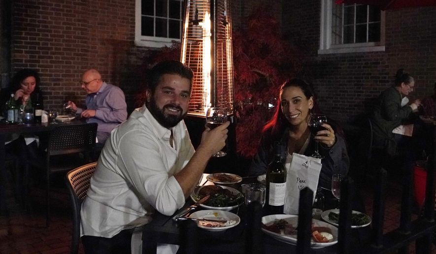 Patrons have dinner outdoors, Friday, Nov. 6, 2020, in Boston's North End. More stringent coronavirus restrictions are now in effect in Massachusetts, including requiring restaurants to stop providing table service at 9:30 p.m. Liquor sales at restaurants and package stores will also shut down at 9:30 p.m. (AP Photo/Elise Amendola)