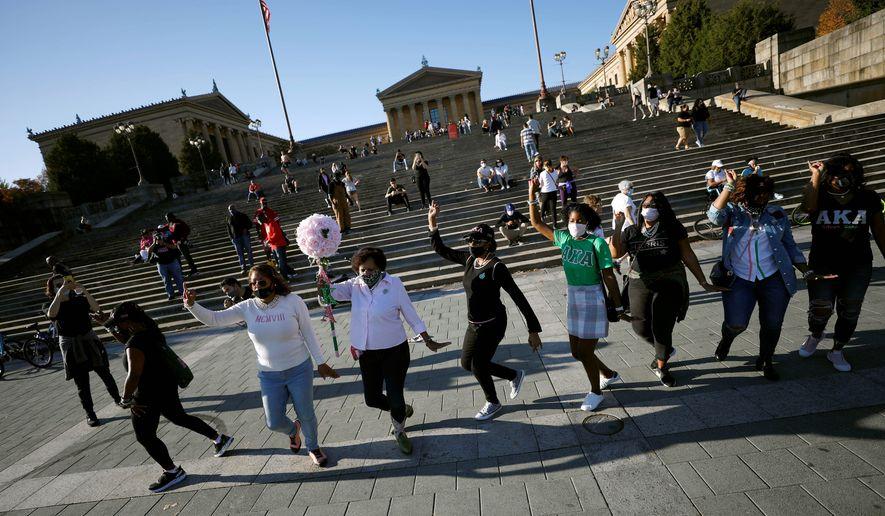 Members of Alpha Kappa Alpha, a Black sorority of which Vice President-elect Kamala Harris is a member, celebrate in front of the Philadelphia Museum of Art in Philadelphia on Sunday. (Associated Press)