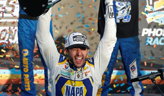 Chase Elliott holds up the NASCAR Cup Series trophy after winning Sunday in Phoenix. He is the third-youngest champion in NASCAR history. (ASSOCIATED PRESS)