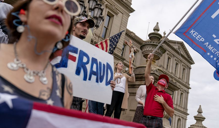 Trump supporters sing the National Anthem while protesting the presidential election results at the State Capitol in Lansing, Mich., Sunday, Nov. 8, 2020. (AP Photo/David Goldman)