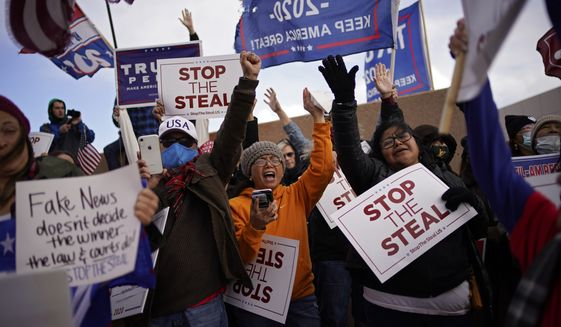 Supporters of President Donald Trump pray as they protest the election outside of the Clark County Election Department, Sunday, Nov. 8, 2020, in North Las Vegas. (AP Photo/John Locher)