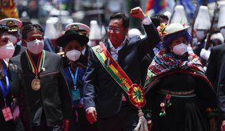 Bolivia's new President Luis Arce, center, raises his fist as he walks with Vice President David Choquehuanca, left, on their inauguration day in La Paz, Bolivia, Sunday, Nov. 8, 2020. (AP Photo/Juan Karita)